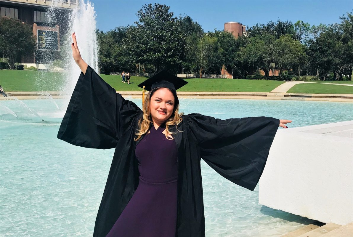 raquel in graduation cap and gown posing in front of reflecting pond