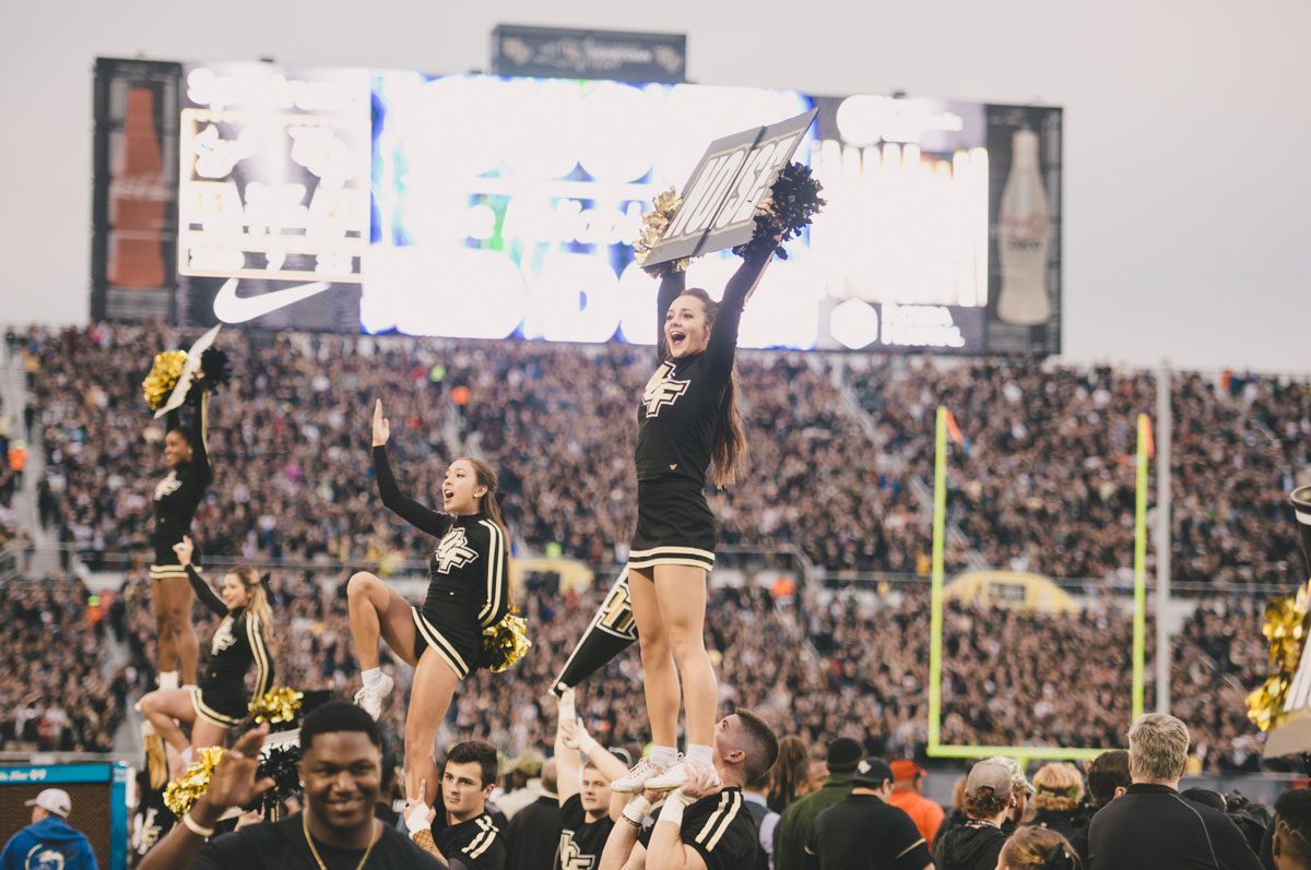 "Cheerleaders dressed in black hold up ""get loud"" signs in front of UCF crowd at Spectrum Stadium"