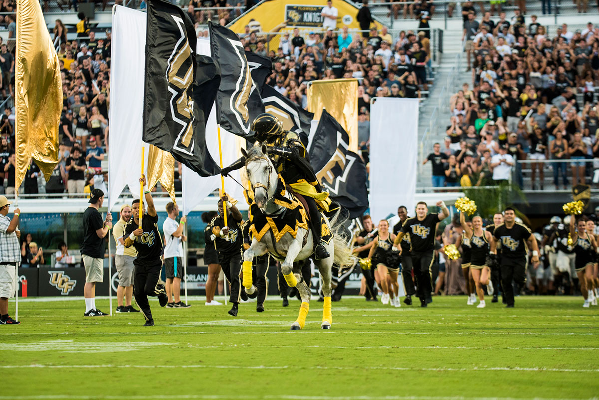 Photo of UCF cheer and Pegasus charging the field