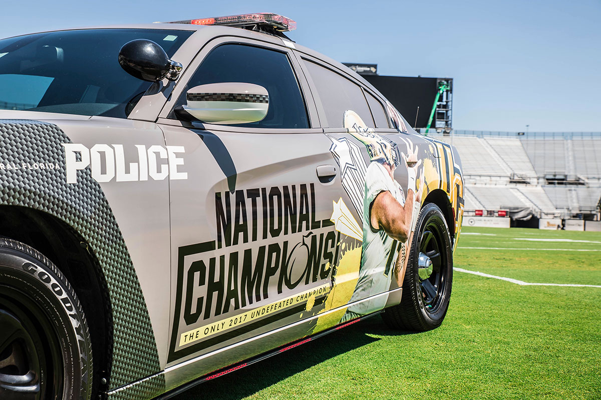 "gray police car with ""national champions"" and image of a receiver detailing the side of the car"