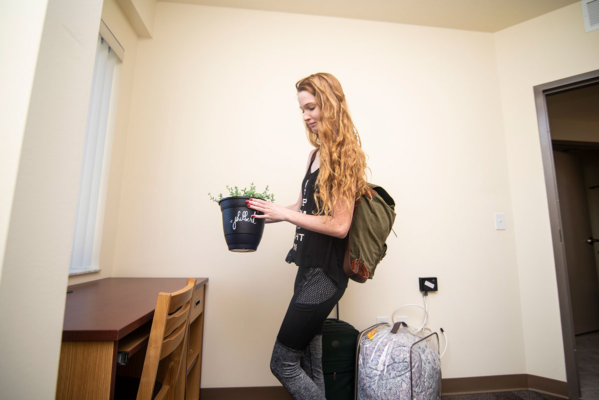 photo of student with her plant in dorm room