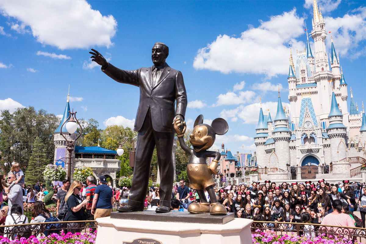 A bronze statue of Walt Disney holding the hand of Mickey Mouse in front of the castle at Magic Kingdom