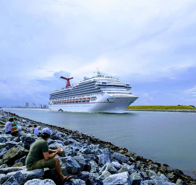 people sitting on rocks watching a cruise ship pass by at Jetty Park at Cape Canaveral