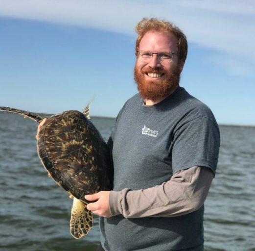ucf student Chris Long holding sea turtle while smiling on boat