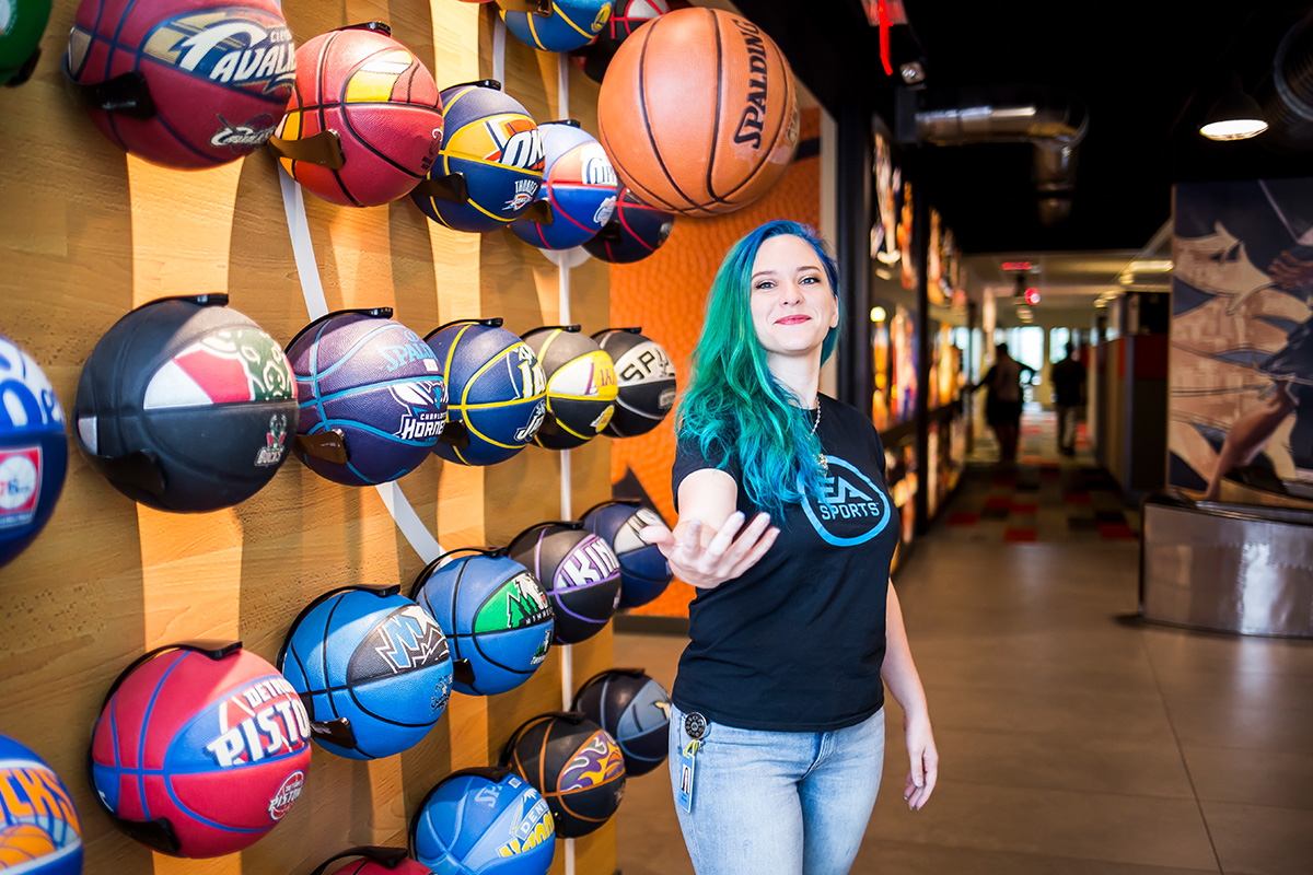 young woman with green and blue long hair, wearing a black t shirt and blue jeans, stands in front of a wall of different color mounted basketballs
