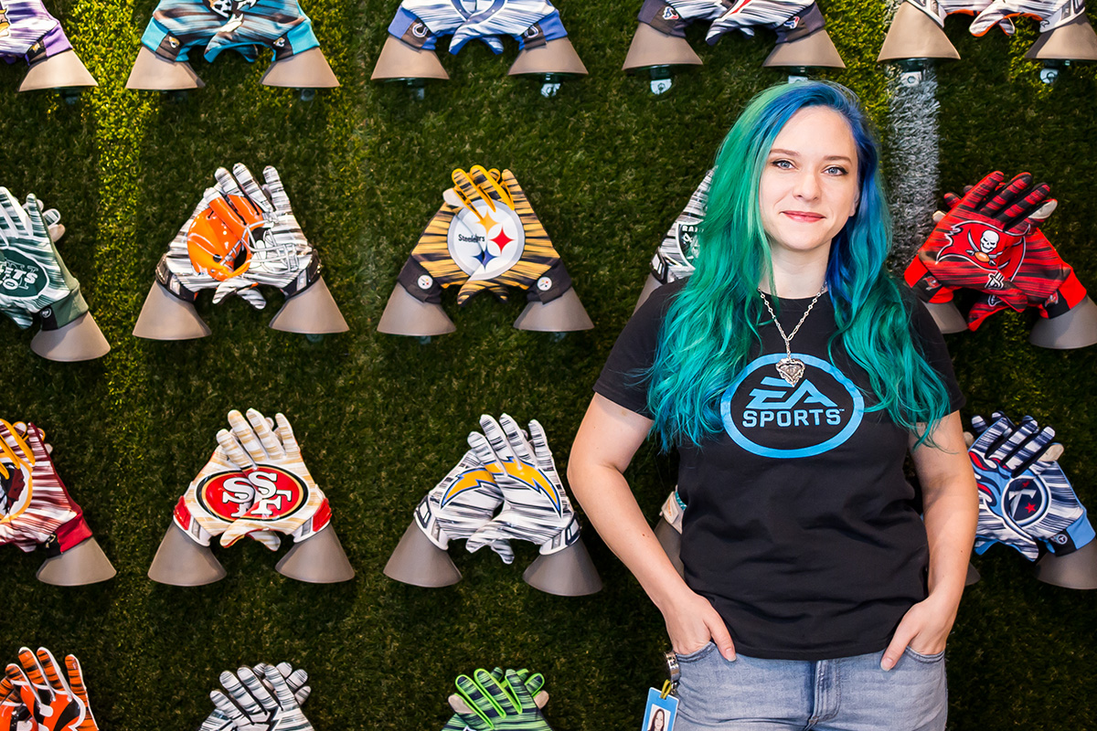 Young woman with blue/green long hair wearing a black t shirt and blue jeans poses with her hands in her front pockets in front of a grass-green wall featuring hand gloves of various NFL teams