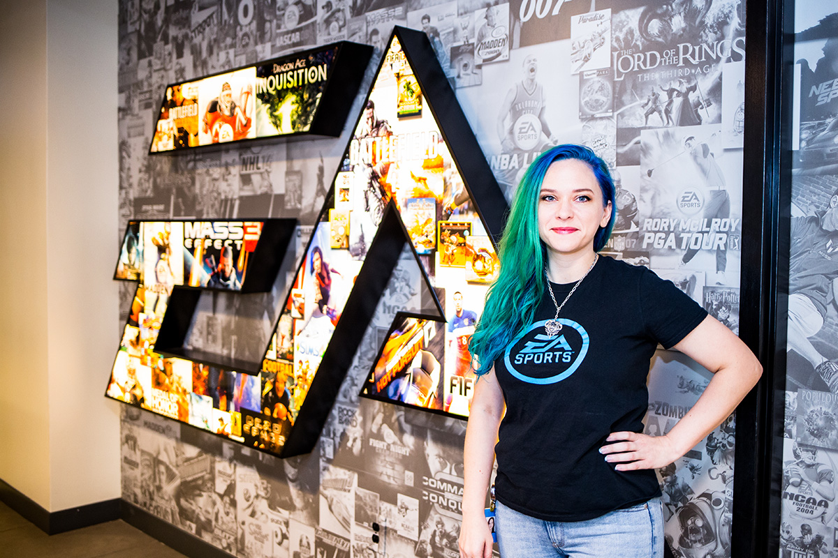 Young woman with blue/green long hair wearing a black t shirt and blue jeans poses with her left hand on her hip in front of black and white wall with multi-color EA sports logo