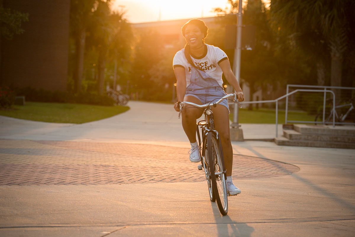 Young woman wearing a white t shirt and jean, short overalls, pedals a silver bike with soft light from sun setting behind her