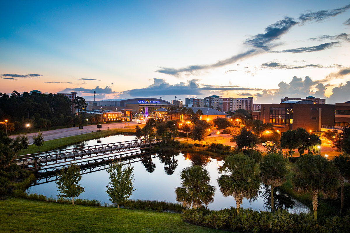Wide view of campus with a pond in the foreground, amber lights and CFE Arena in the back as the sun rises