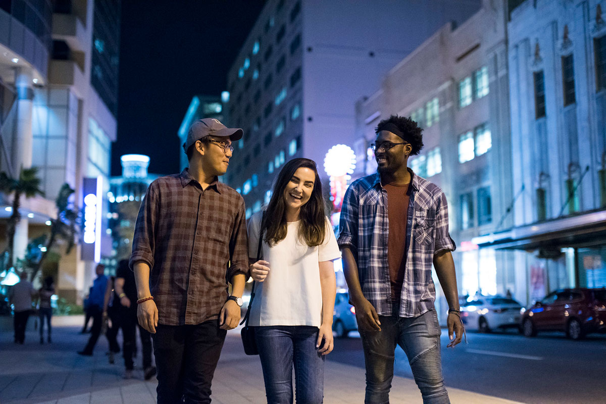 A young adult female with brown hair, white t shirt and blue jeans, walks downtown at night flanked by two men, one wearing a baseball cap, flannel shirt and jeans and the other wearing glasses, a black head band, blue open button flannel with a red-brown shirt underneath and blue jeans.