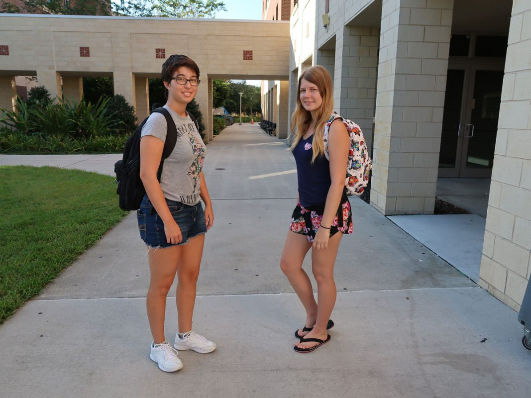 Two female students wearing t shirts and shorts pose on a sidewalk with backpacks over their shoulders