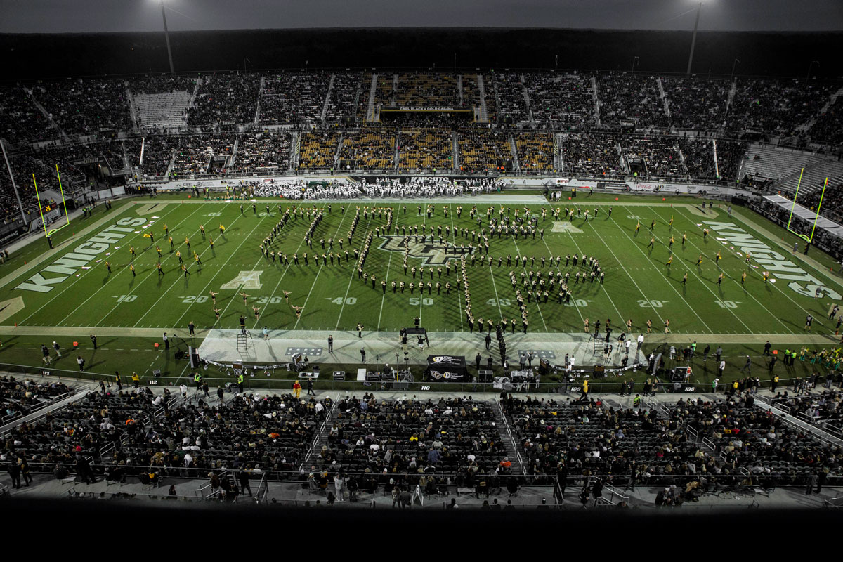 wide shot of a football stadium at night with UCF logo spelled out by the band on the green field