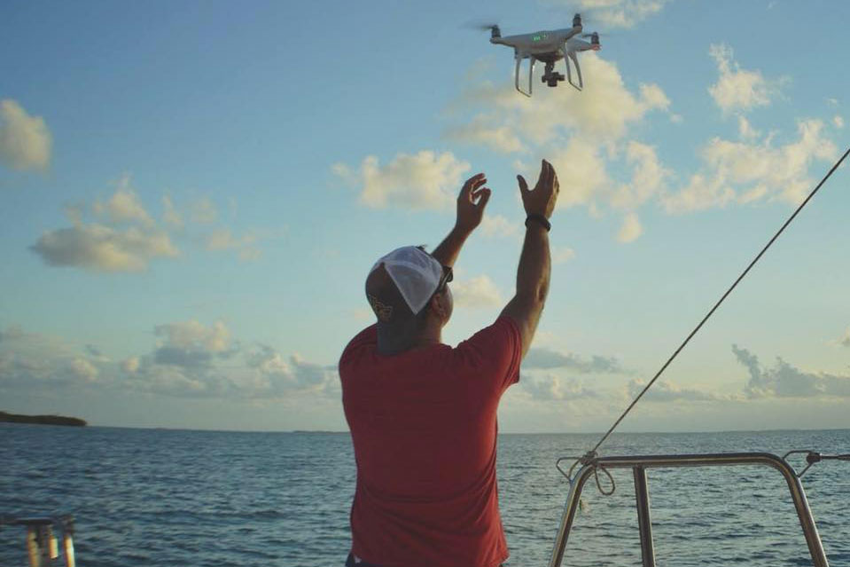 Man in a red shirt and baseball hat releases flying drone from boat