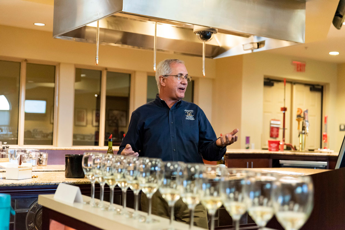An older man with gray hair wearing a navy blue shirt gestures in front of a row of wine glasses