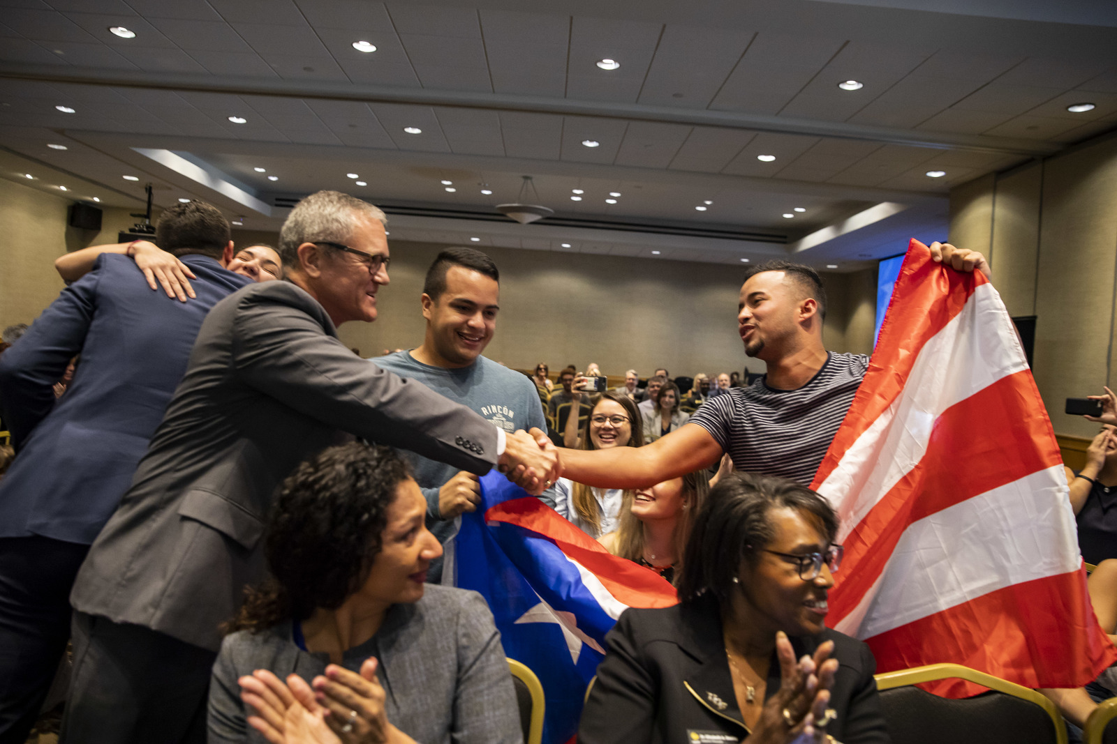 President Whittaker shakes hands with members of the Puerto Rican Student Association.
