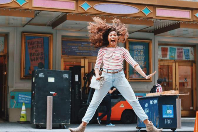 A young adult woman dressed in jeans and a pink long sleeve shirt jumps in front of a Broadway theater