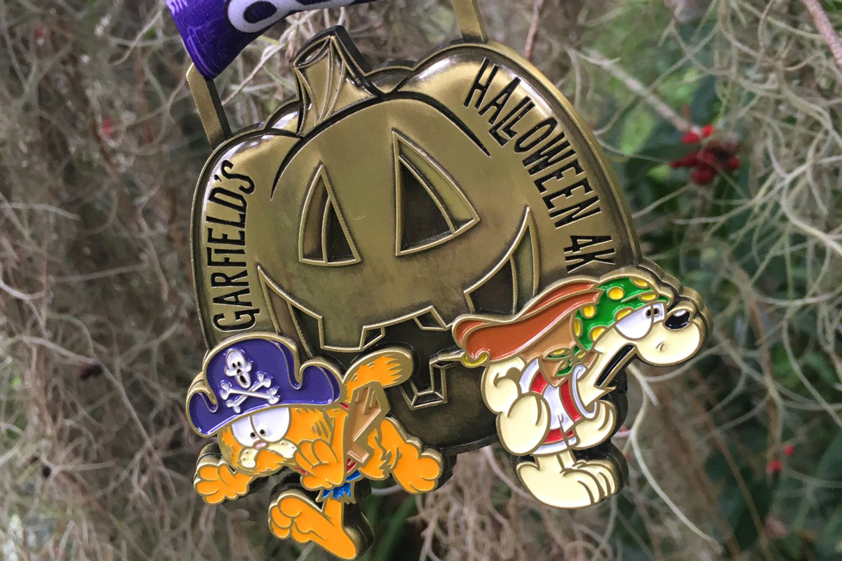a bronze-color medal shaped like a jack-o-latern with cartoon Garfield and Odie dressed in costume attached to it)