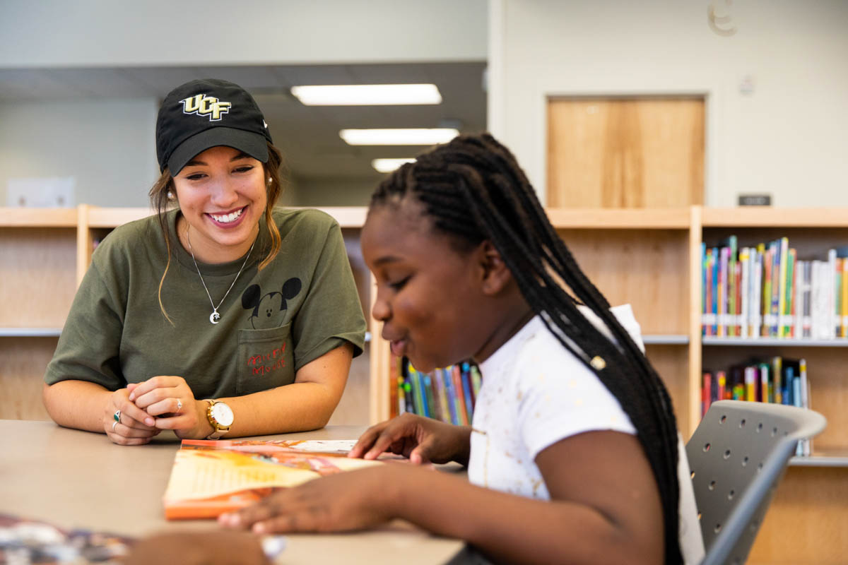 As an intern for UCF Downtown, senior writing and rhetoric major Melissa Mitchum works with an elementary school student.
