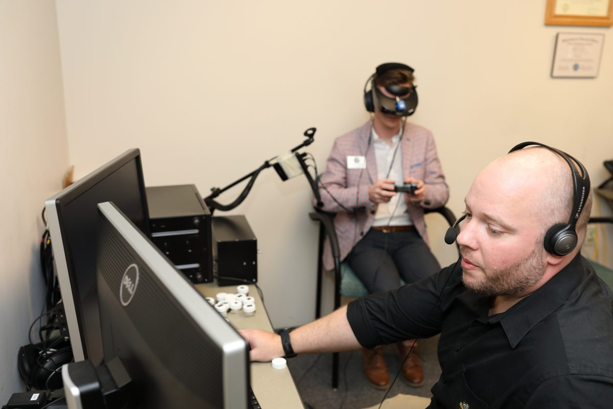 A bald man wearing headphones sits at a desk looking at a computer with another person sitting behind him wearing a VR headset