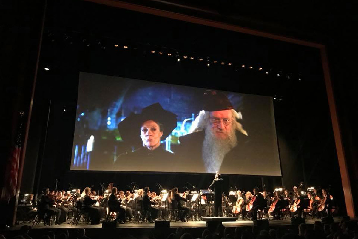 orchestra playing on stage under a movie screen depicting Harry Potter characters