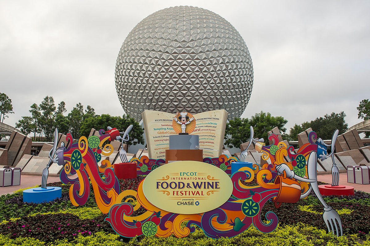 Orange, red, yellow and purple sign announcing food and wine festival in front of EPCOT monument