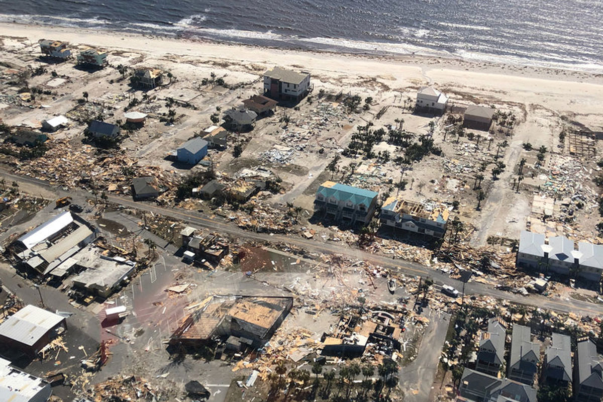 aerial view of homes ruined by hurricane damage with a beachline and ocean in view