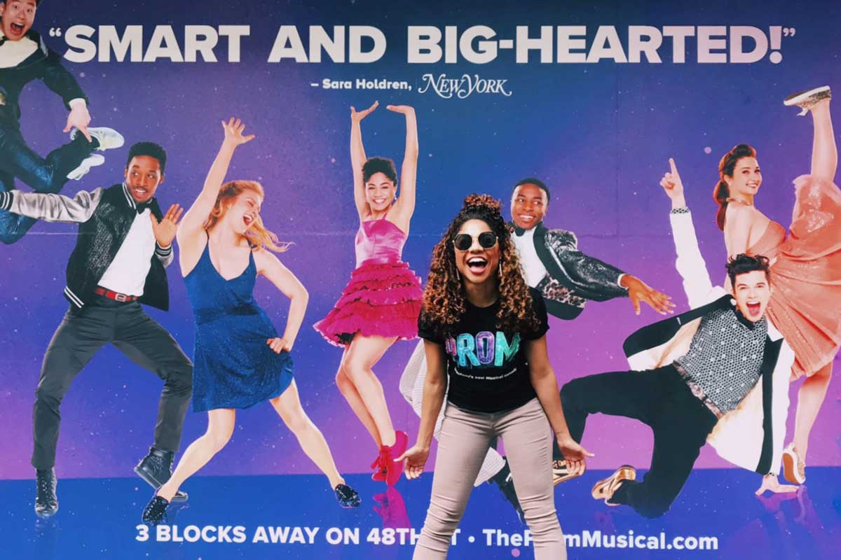 "African-American woman wearing black shirt and khaki pants stands in front of billboard ad with text ""Smart and Big-Hearted!"""