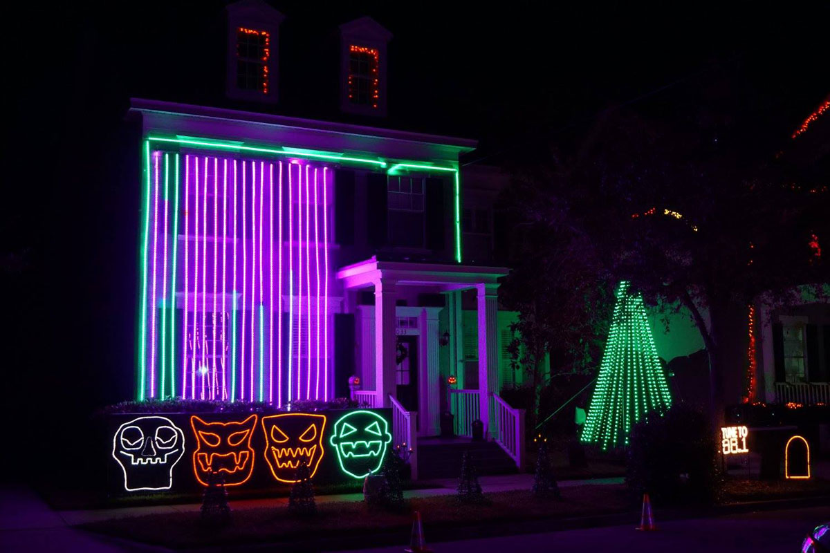 two-story home lit up at night by green and purple neon lights