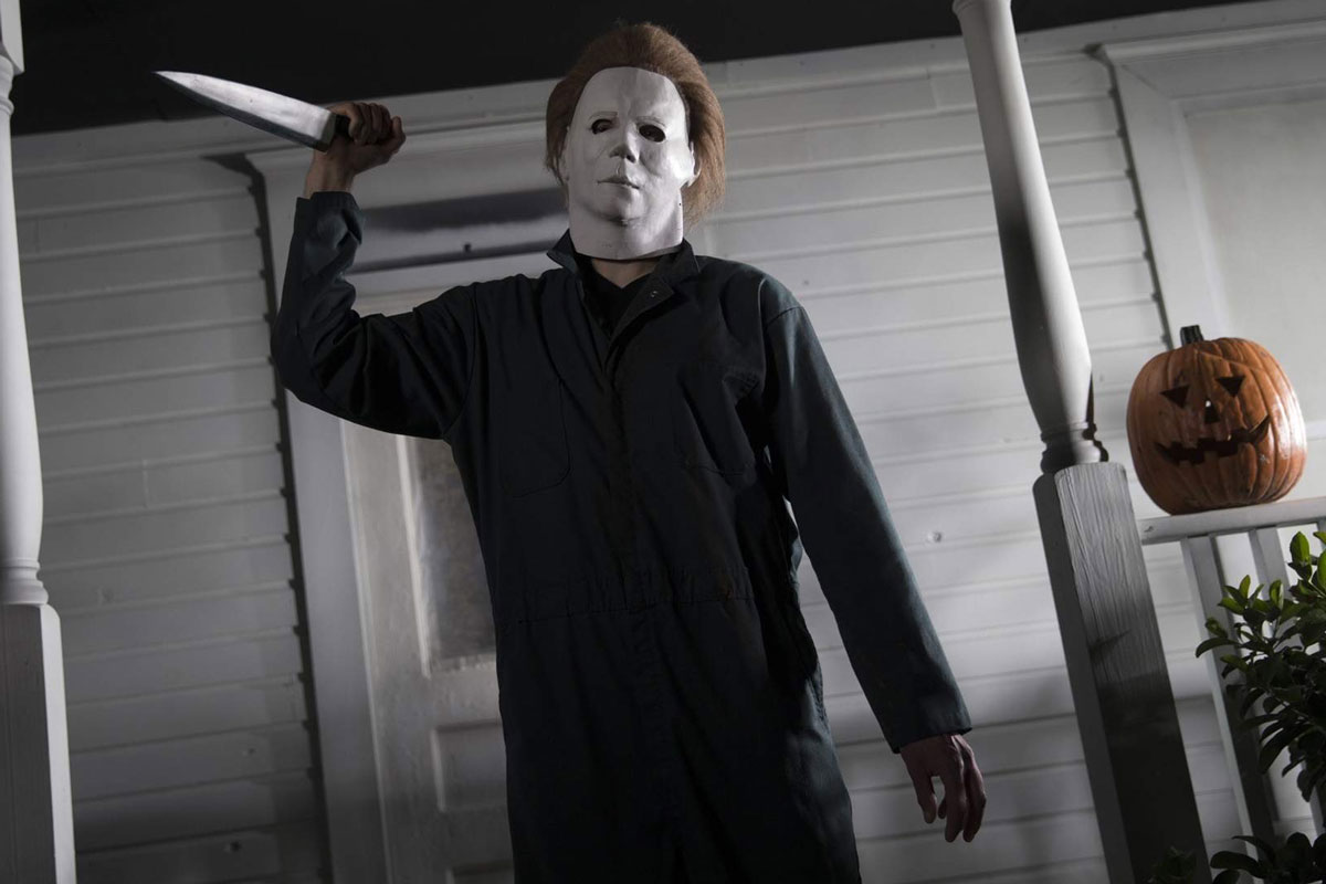 Michael Myers from the film Halloween holds a knife on a white front porch with a jack-o-lantern beside him