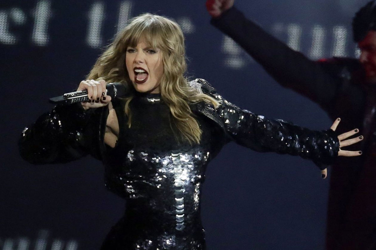 taylor swift singing into a microphone while wearing a black long sleeve body suit