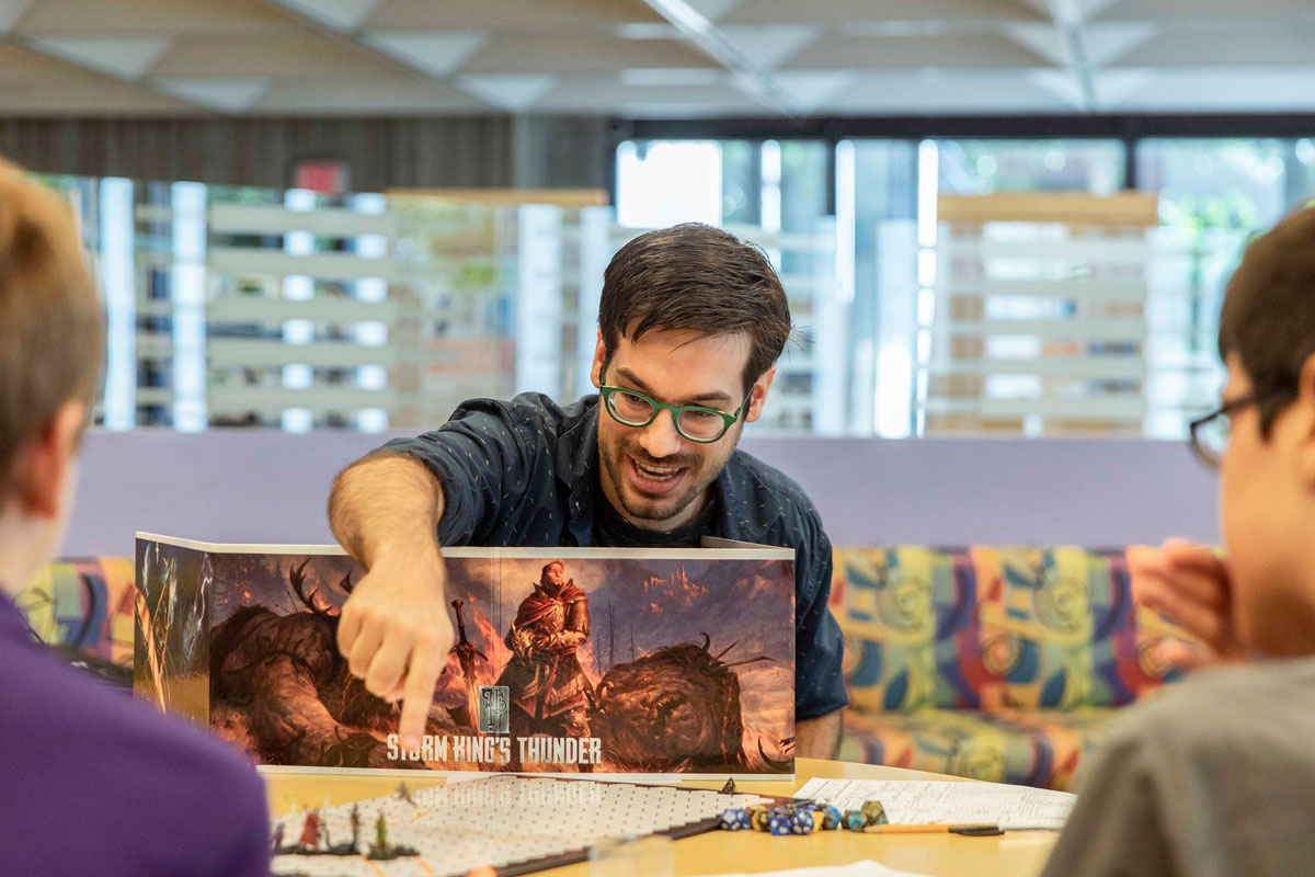 A man with dark hair and wearing glasses reaches over a book standing upright in front of him and points to a piece on a gaming board.