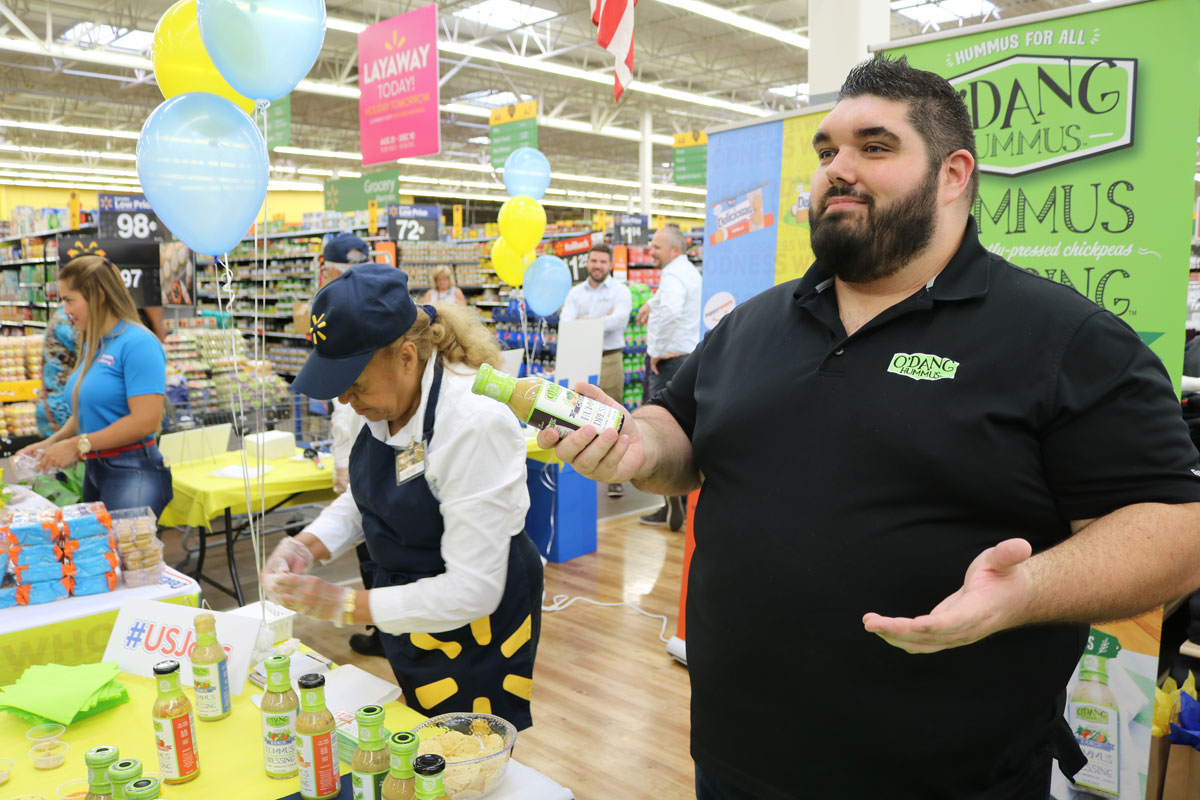 Man with dark hair and a dark beard wearing a black polo shirt stands in front of a table with green salad dressing bottles in a Walmart store