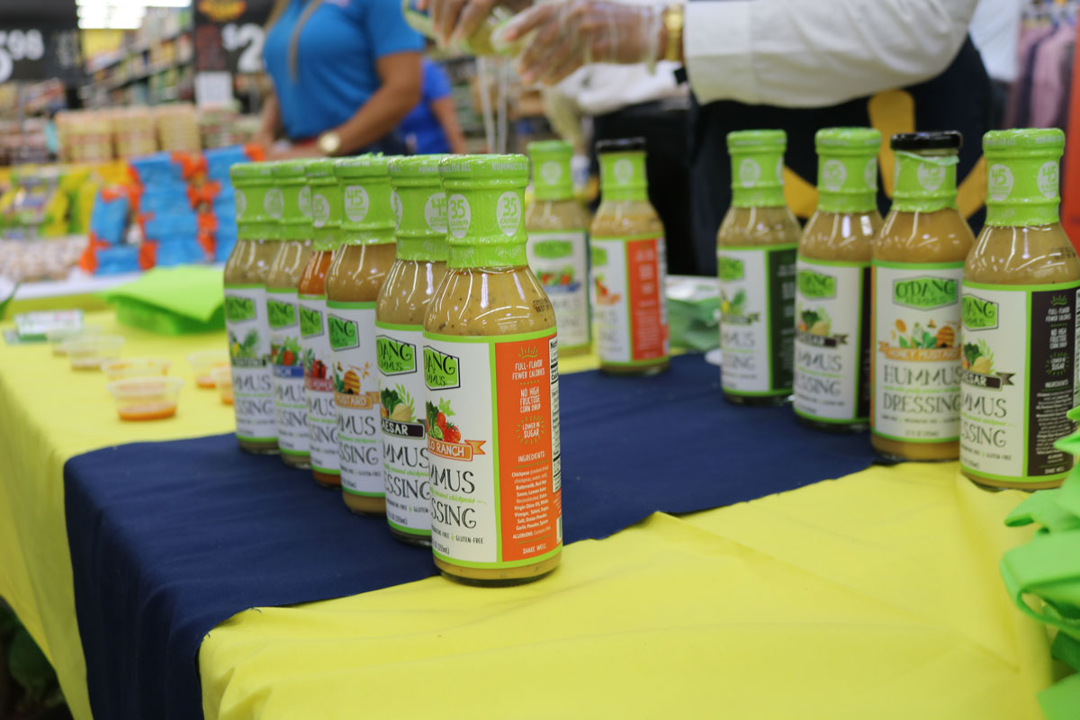 rows of salad dressing bottles with green tops on a table with a blue and yellow table cloth