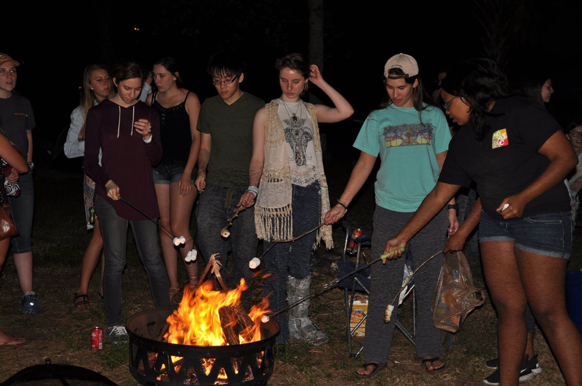 Group of students roasting marshmallows at night over a campfire