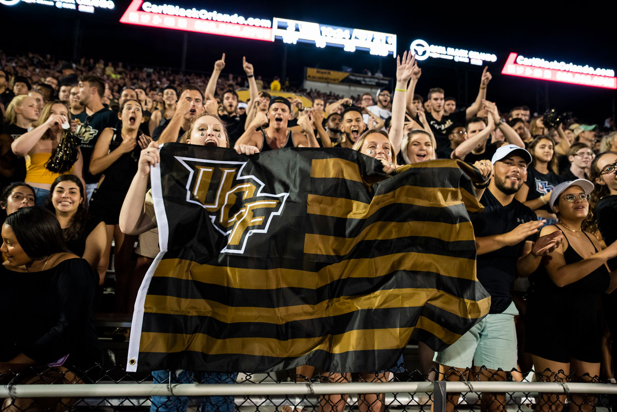 Fans cheering in the stands at night waving a UCF black and gold flag
