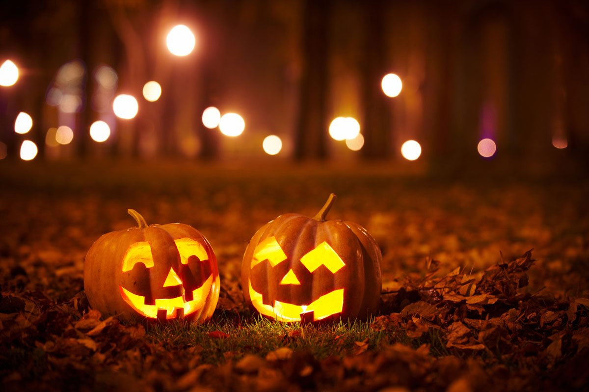two lit-up jack-o-lanterns on the ground with trees and lights blurred in the background
