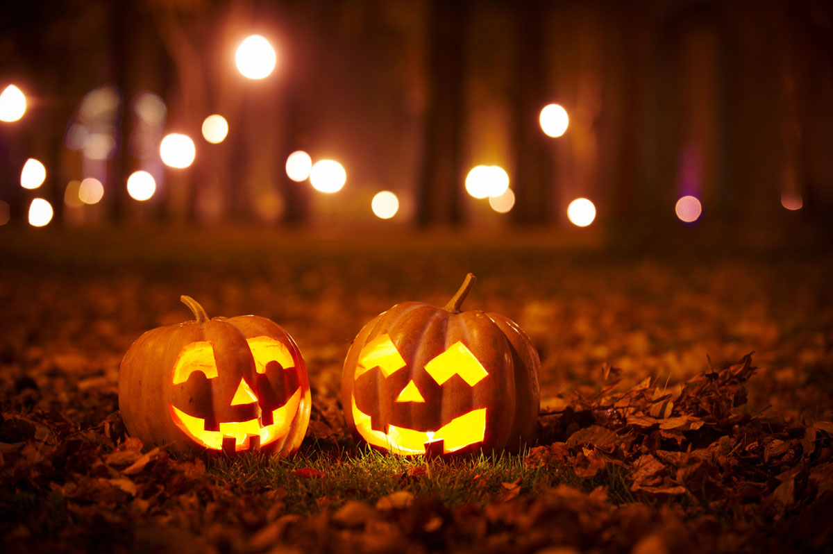 two lit up jack o lanterns on the ground with trees and lights