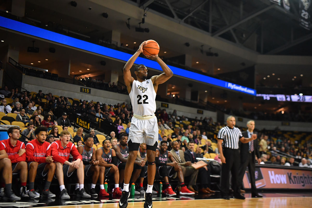 UCF men's basketball player Chance McSpadden in a white uniform pulls up for a 3-point shot in front of opposing bench