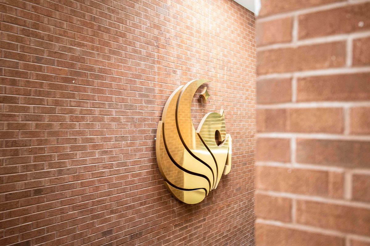 brick wall with a shiny, gold pegasus logo fixture