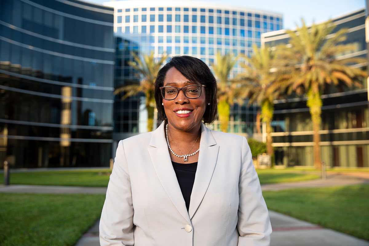 Provost Elizabeth Dooley, wearing a tan blazer, in front of the UCF Teaching Academy