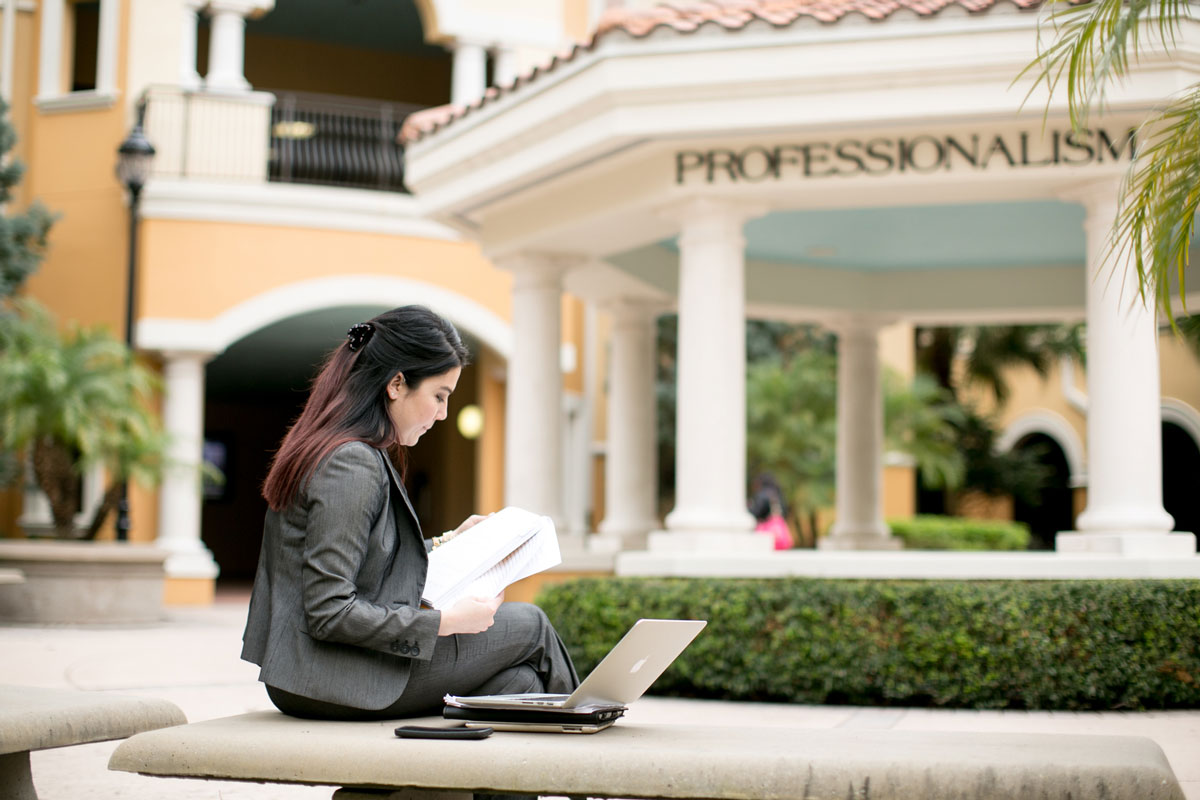 A woman with dark hair and wearing a gray business suit sits on a concrete bench with a laptop in front of a rotunda with white columns outside