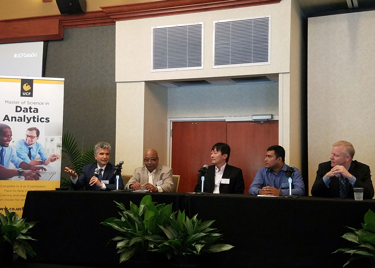 A panel of five men sitting at a table with green plants around it and a poster advertising UCF's data analytics program