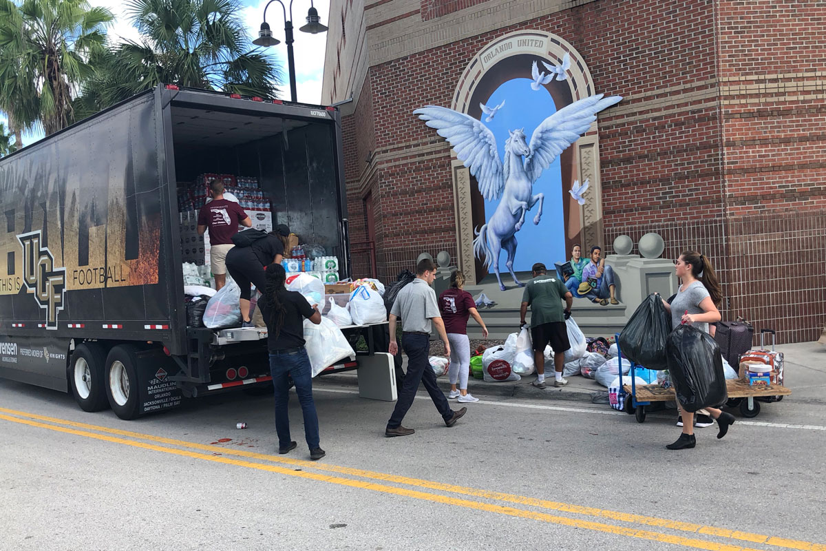 A group of people load bags of supplies into a moving truck outside of UCF's Student Union