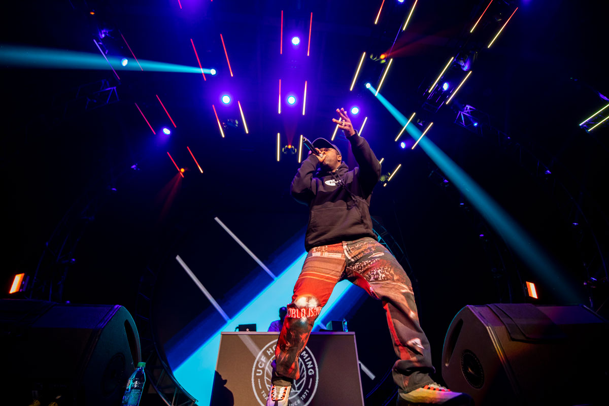 a man wearing multicolor red pants and a black long sleeve shirt holds a microphone with blue lasers shining around him on stage