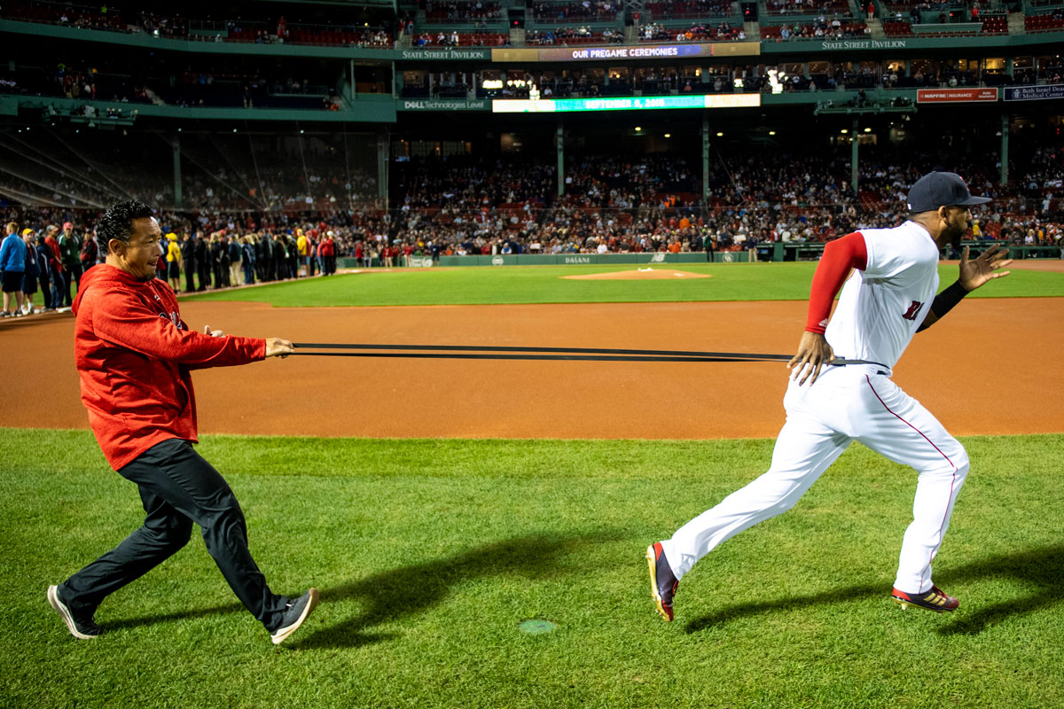 David Price of the Boston Red Sox runs with a long band around his waste with a man in a red sweatshirt and dark pants pulling behind him