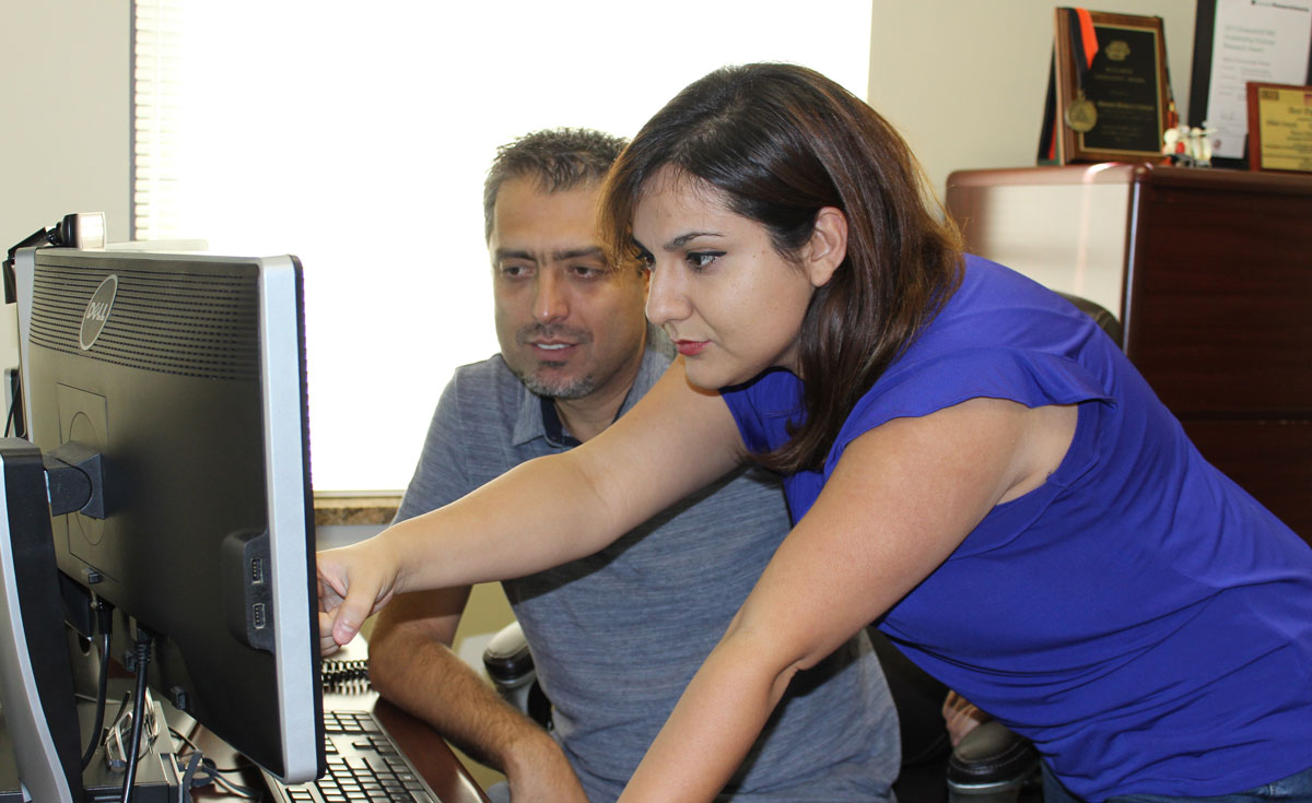 A man and a woman look at a computer screen in an office