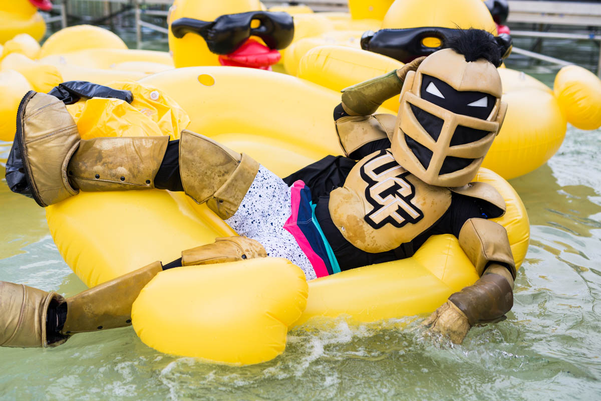 Knightro wears swim trunks and lays in an inflatable duck while floating on the water.