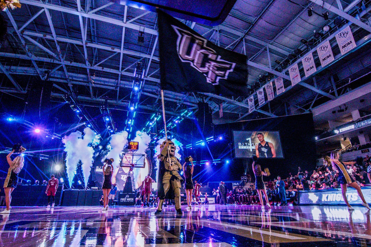 UCF mascot Knightro waves black UCF flag on court at CFE Arena with cheer team around him