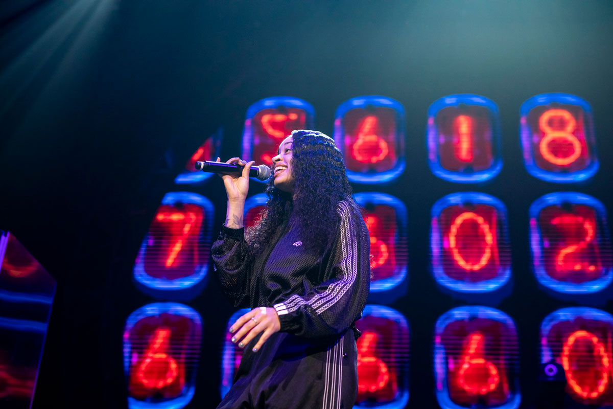 a woman in a black track suit sings in front of neon red numbers