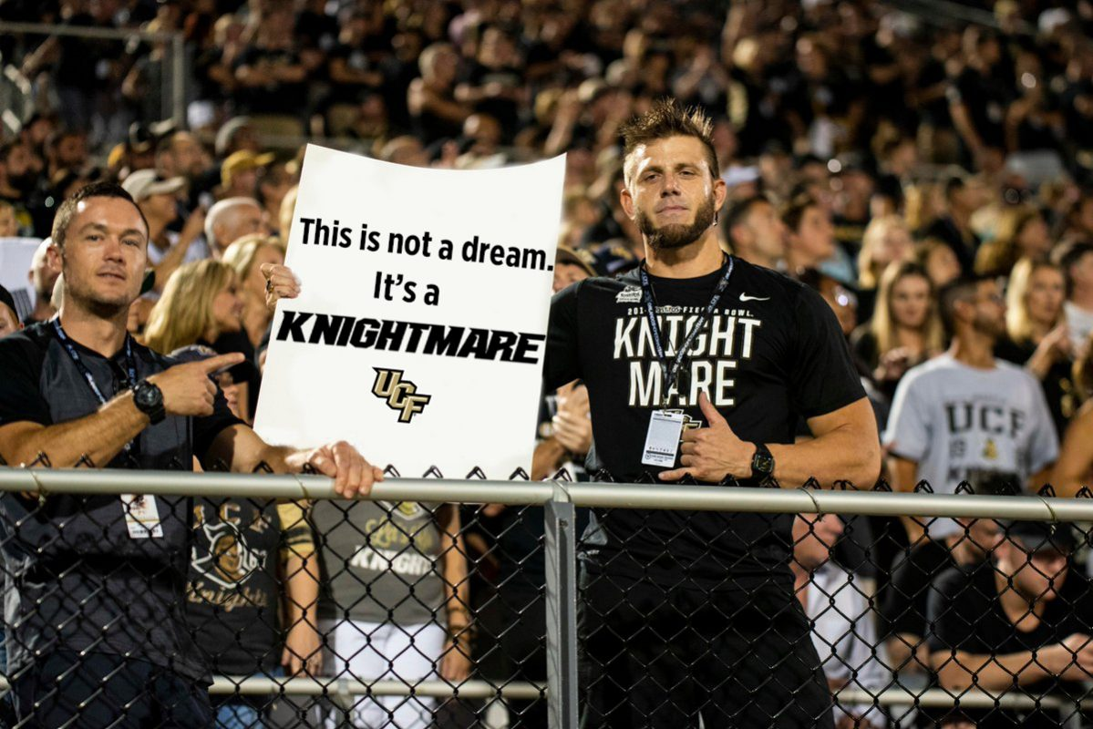 "Two football fans wearing black t shirts hold a white sign that reads ""This isn't a dream. It's the Knightmare"""